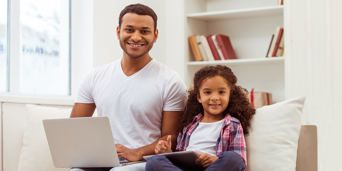 Father with daughter doing remote learning