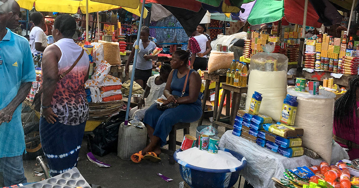 A woman sits behind a stall in a busy market