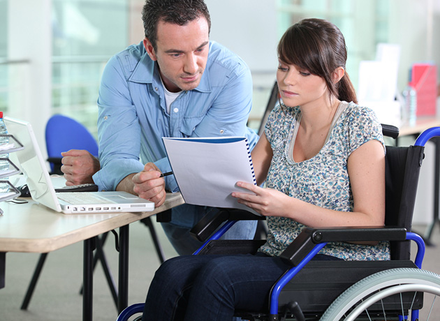 woman in a wheelchair working with male colleague