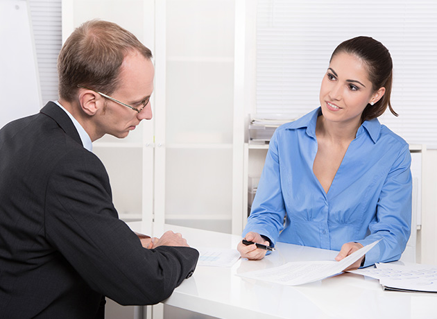 photo of woman interviewing man in suit